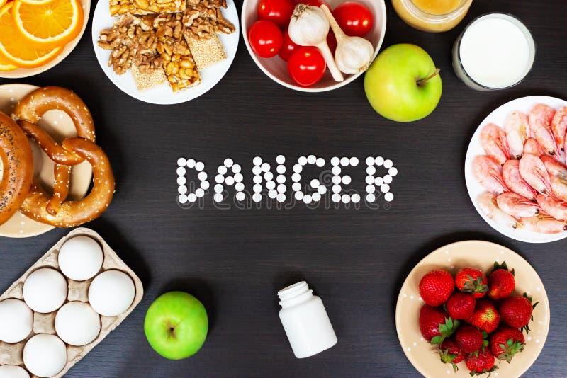 设置与抗组胺药片的过敏食物在木桌上 免版税库存照片