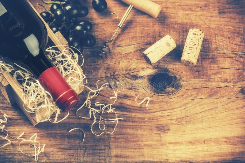 设置与瓶红葡萄酒、葡萄和黄柏 浓缩的酒类一览表 图库摄影