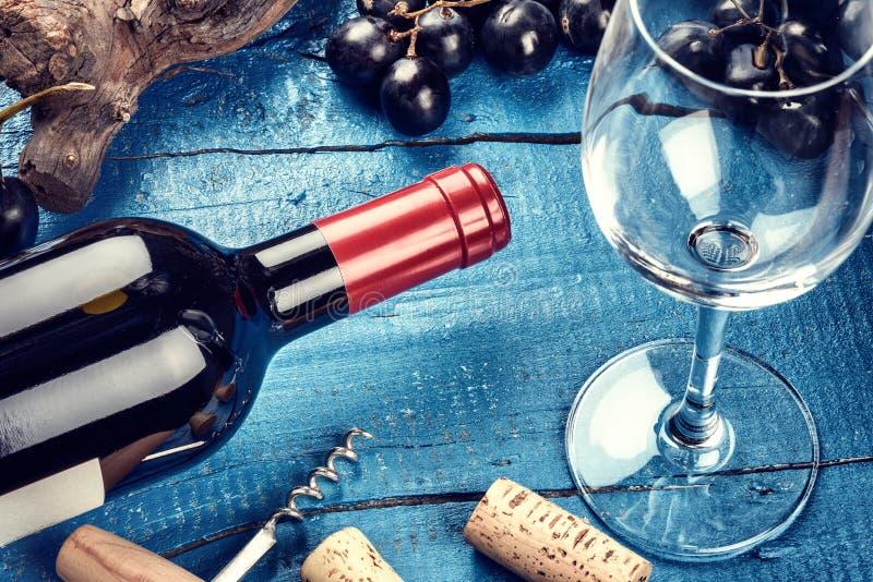 设置与瓶红葡萄酒、葡萄和黄柏 浓缩的酒类一览表 免版税图库摄影