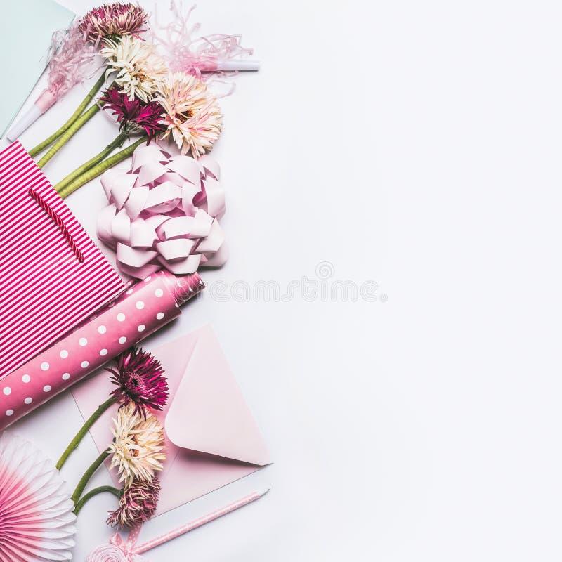设置与花、弓、丝带、桃红色礼品包装材料纸和购物袋的问候辅助部件在白色桌面背景 免版税库存照片