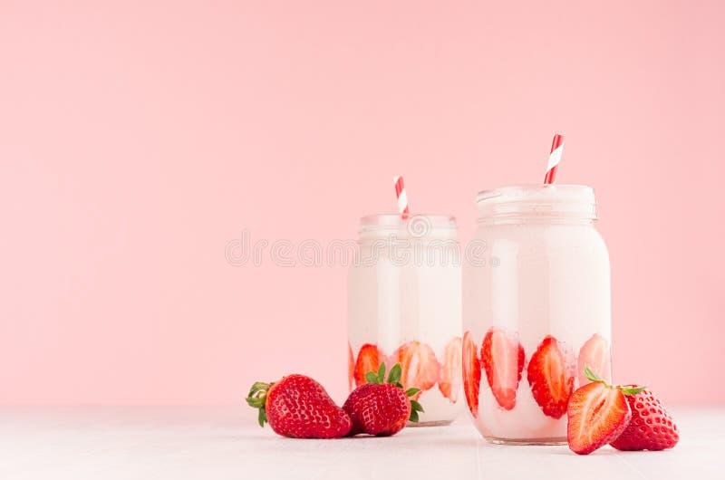 设置两在行家瓶子的新鲜的冷的奶昔用被切的成熟莓果,在高雅桃红色厨房内部的镶边秸杆 库存照片