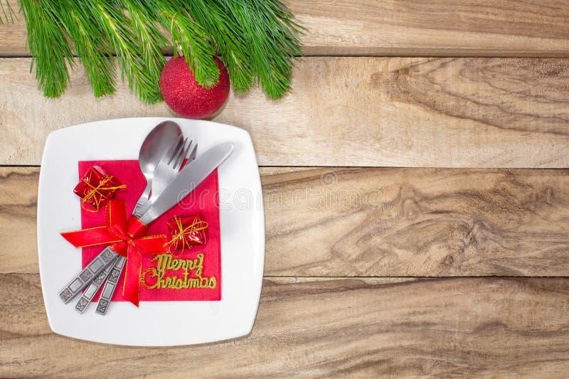 设置为圣诞节桌、蜜桔、装饰、冷杉和一块板材有礼物和利器的 欢乐的背景 使用大方的本体sp 库存照片