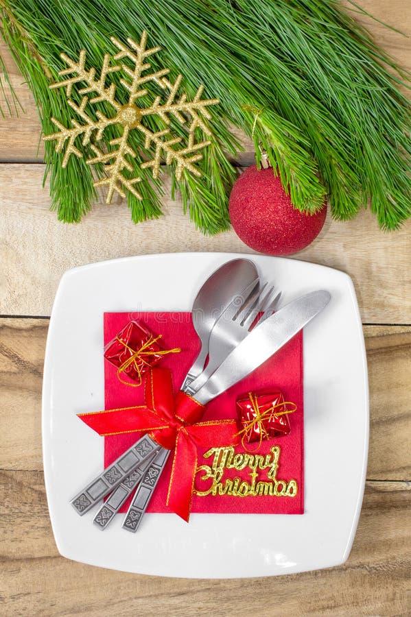 设置为圣诞节桌、蜜桔、装饰、冷杉和一块板材有礼物和利器的 欢乐的背景 免版税库存照片