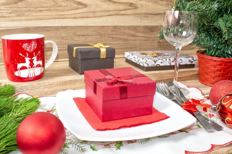 设置为圣诞节桌、蜜桔、装饰、冷杉和一块板材有礼物和利器的 库存照片