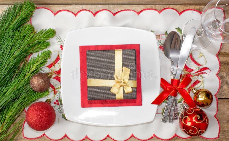 设置为圣诞节桌、蜜桔、装饰、冷杉和一块板材有礼物和利器的 免版税库存图片
