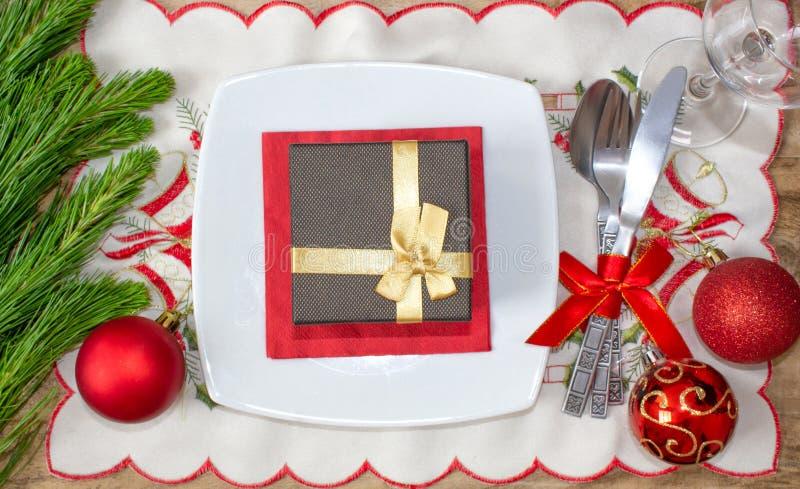 设置为圣诞节桌、蜜桔、装饰、冷杉和一块板材有礼物和利器的 免版税库存照片