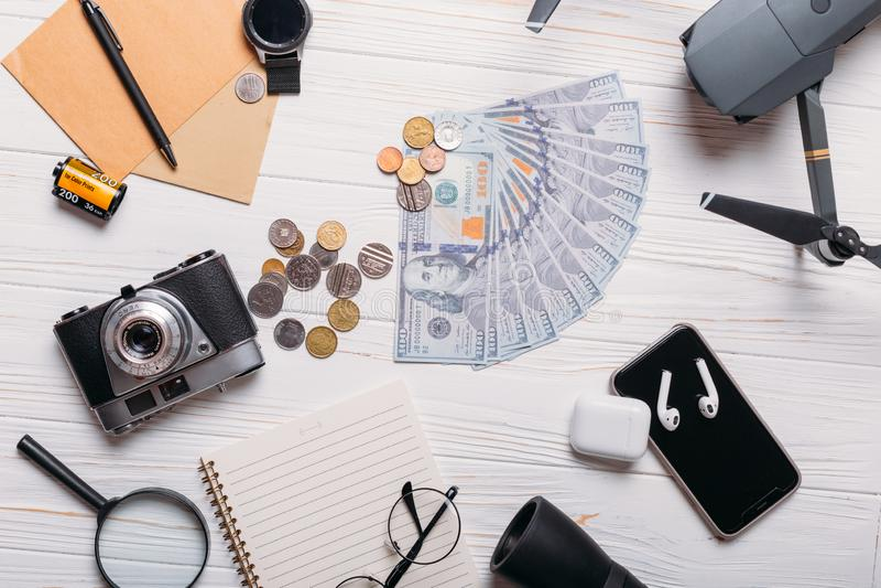 设置为在白色背景的旅行:金钱、照相机、寄生虫、电话和其他辅助部件平展放置 图库摄影