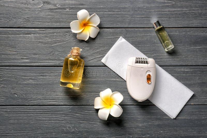 设置为有油的头发去除和瓶在黑暗的木桌上 免版税库存照片