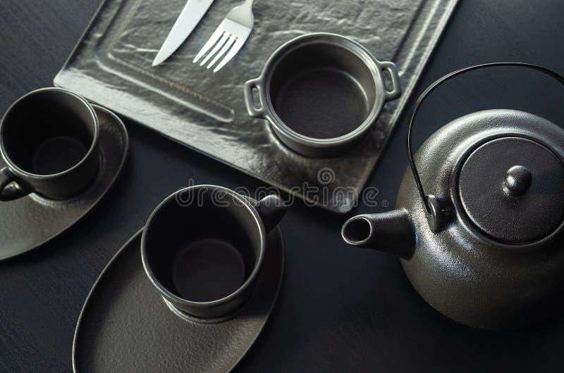 设置为茶道 大黏土茶壶和杯子在木背景 ?? 复制空间,文本的空间 库存图片