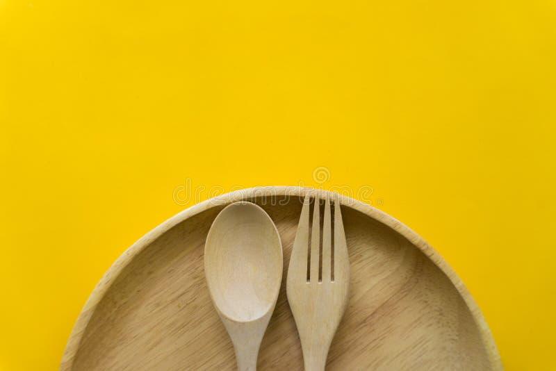设置叉子、匙子和盘木头有黄色背景 免版税库存图片
