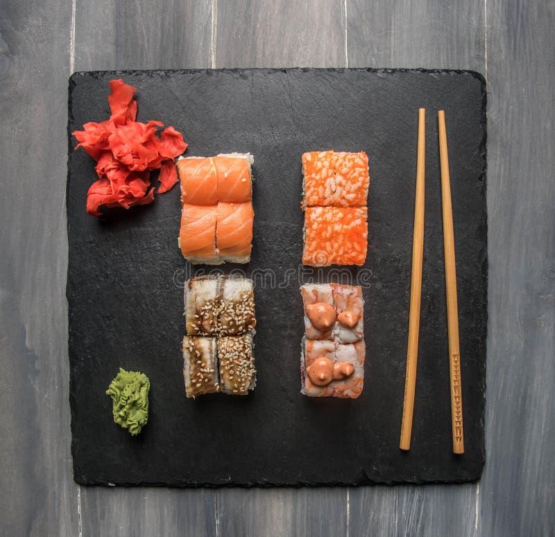 设置可口寿司用姜、酱油和山葵在一个黑石盘子,在灰色背景,顶视图 免版税库存图片