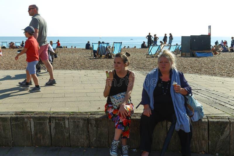 设置在吃冰淇凌的海滩的路一边的两白种人人 r 免版税库存图片