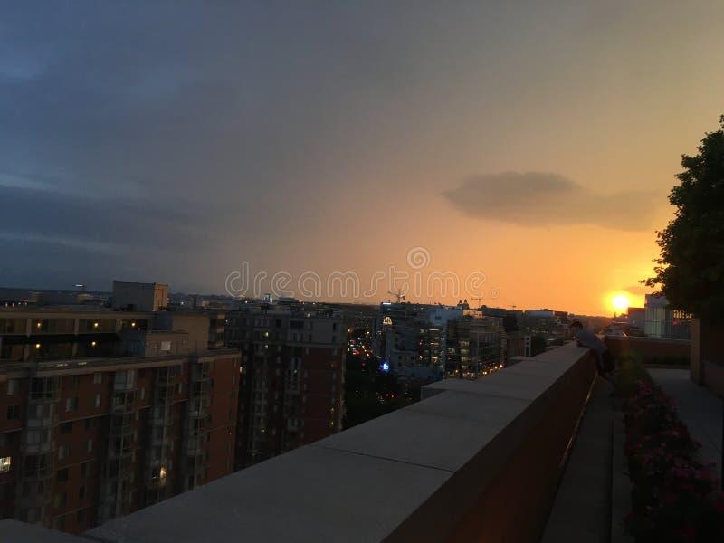 设置在城市的橙色太阳 免版税库存照片