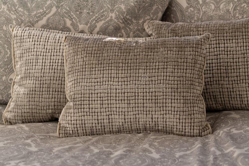 设置在床上的淡色,白色和浅灰色的坐垫或枕头 免版税图库摄影
