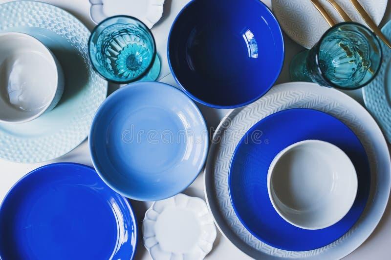 设置在蓝色口气的餐具 陶瓷板材和酒杯 免版税库存图片