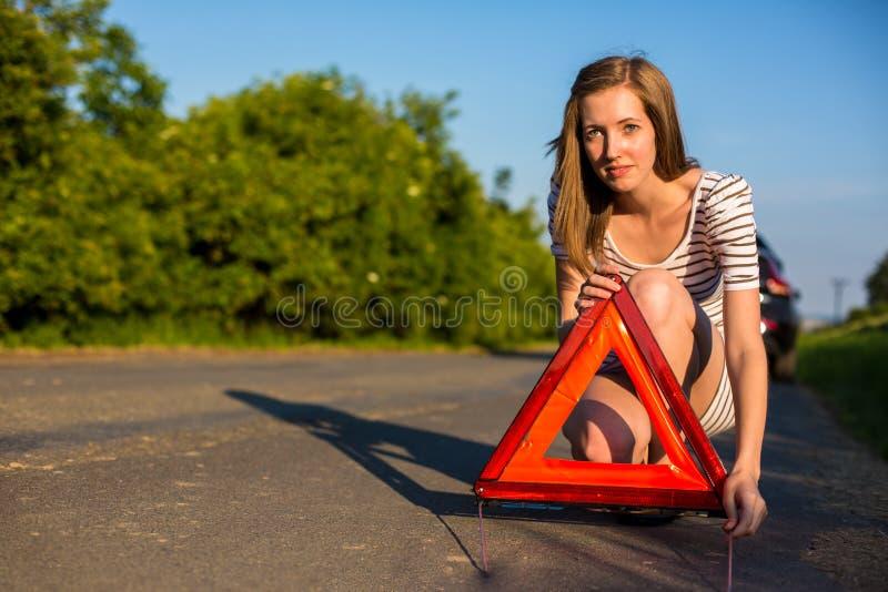 设置在路旁的俏丽,少妇安全三角 库存照片