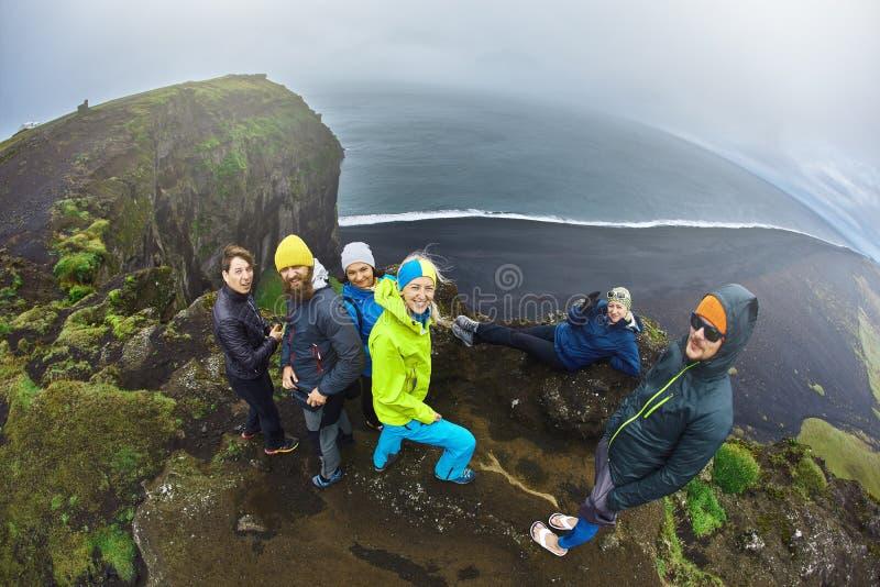 设置在Dyrholaey峭壁,冰岛的游人 免版税库存照片