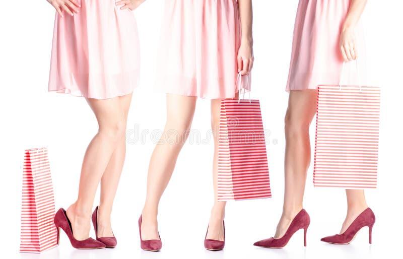 设置妇女腿以红色高跟鞋鞋子和礼服袋子包裹手中时尚 库存图片