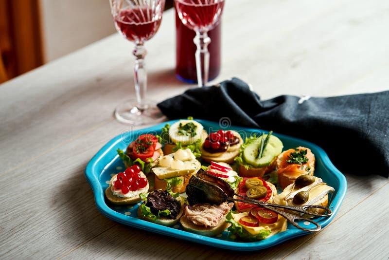 设置微型三明治或塔帕纤维布两的与杯酒在一张木桌上 免版税图库摄影