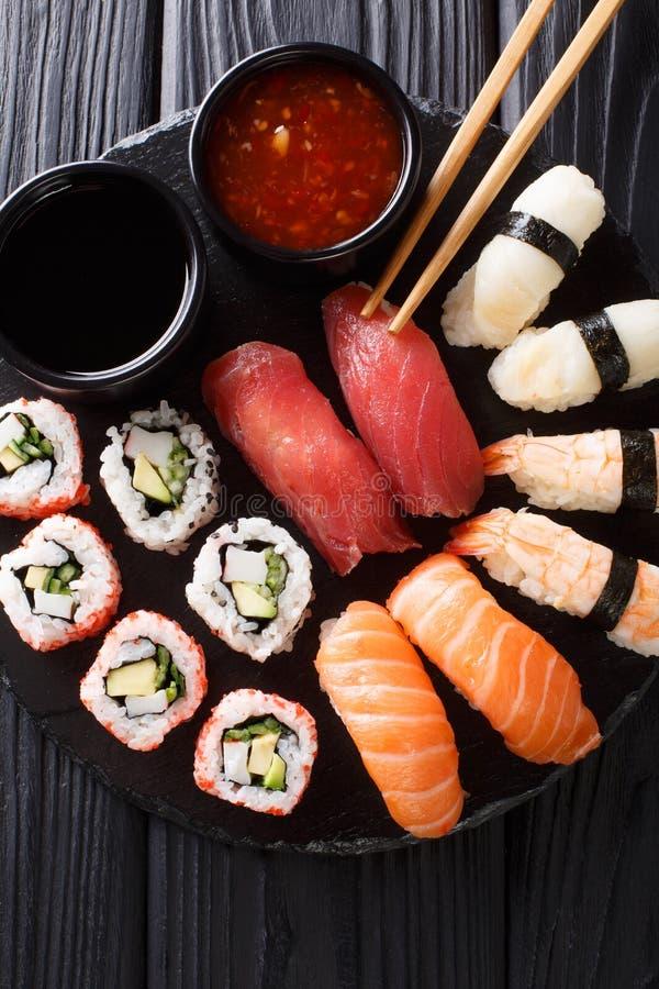 设置新鲜的maki、uramaki和nigiri寿司,供食在黑色的盘子 垂直的顶视图 库存照片