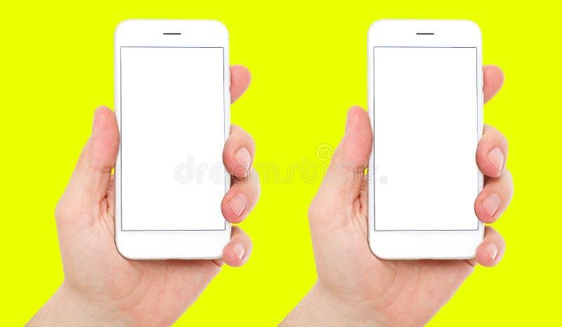设置有在黄色背景隔绝的空的空白的显示的两个电话,男性手拿着电话垂直,2智能手机 免版税库存照片