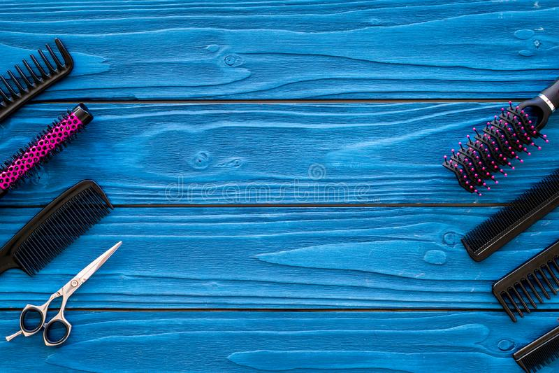 设置有梳子蓝色木背景顶视图copyspace的专业美发师工具 免版税库存图片