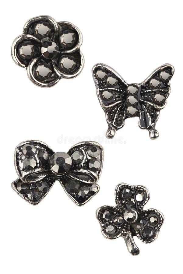 设置有黑金刚石花,蝴蝶、弓和三叶草叶子的四副不同银色耳环,隔绝在白色背景 免版税库存照片