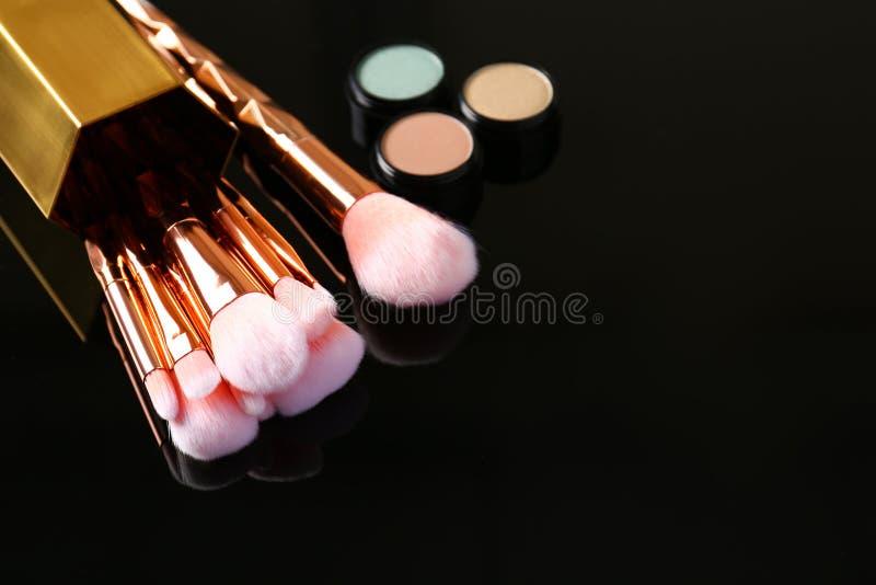 设置构成刷子和化妆用品在黑暗的背景 免版税库存照片