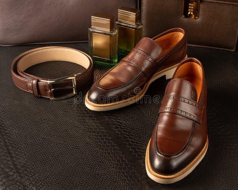 设置棕色人的鞋子、腰带和两个瓶在棕色人的公文包背景的人的香水  库存照片