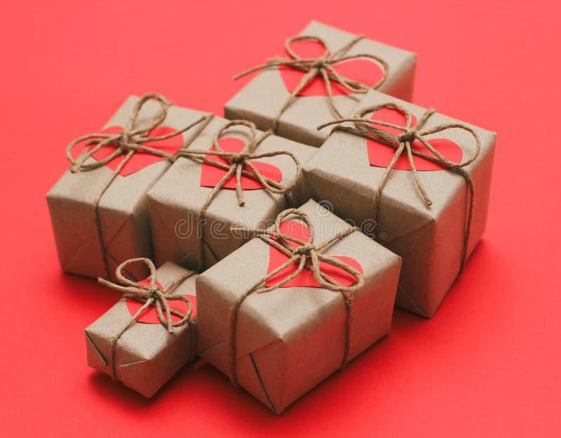 设置棕色礼物盒 包裹在工艺纸和栓由大麻绳子 明亮的红色背景和纸盒心脏装饰卡片 免版税库存图片
