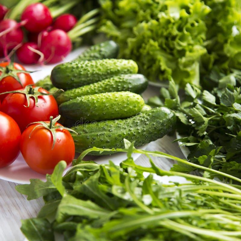 设置沙拉做的各种各样的有机成份:蕃茄,萝卜,黄瓜,芝麻菜,莴苣,侧视图 健康的食物 关闭 库存图片
