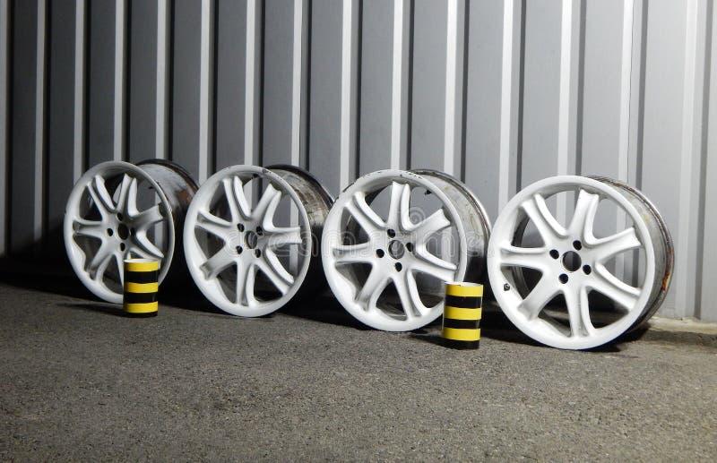 设置生锈的损坏的合金轮子为装边在车库 免版税库存照片