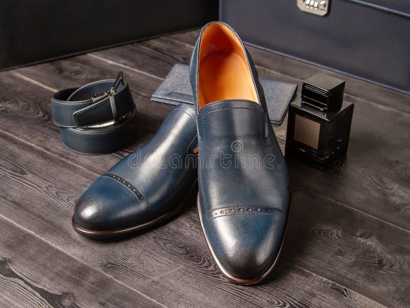 设置经典人的蓝色鞋子、钱包、裤子传送带和一个瓶在木板走道背景的人的香水 免版税库存图片