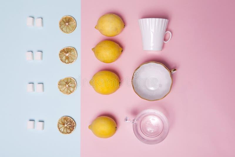 设置茶 精制糖、柠檬、桔子、杯子和匙子作为一件装饰品在一张桃红色和蓝纸 免版税库存图片
