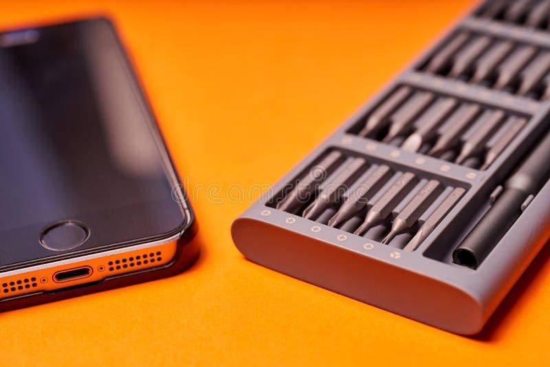 设置螺丝刀和电话的微型位在橙色背景 免版税库存图片