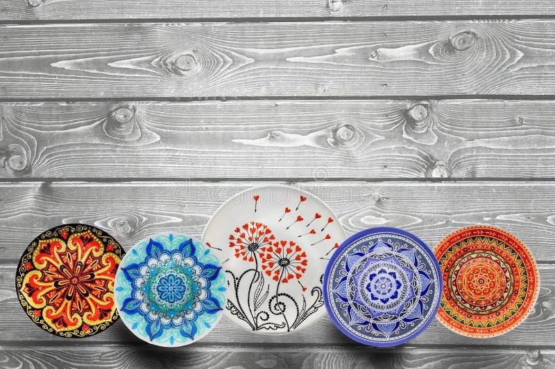 设置装饰陶瓷与丙烯酸漆的板材手画光点图形在灰色木背景 r 库存图片
