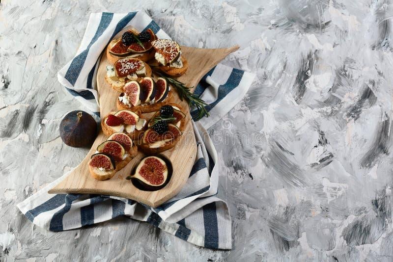 设置bruschettas用无花果、乳酪、蜂蜜和核桃在烤有壳的面包在黑背景绝缘的一个木板 Fl 库存照片