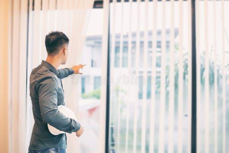 设计亚裔的人拿着工作的白色安全帽在offi 免版税图库摄影