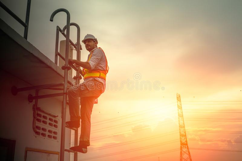 设计工作在梯子的技术员修理电缆绳 免版税库存图片