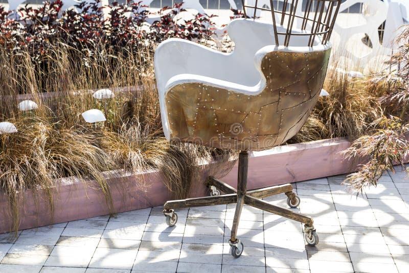 设计师与铆钉的金属与轮子的椅子和铁锈 免版税库存图片