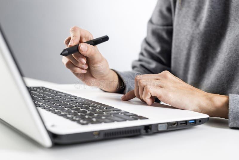 设计师坐在办公桌前,在笔记本电脑工作 免版税库存图片