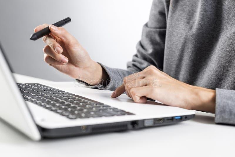 设计师坐在办公桌前,在笔记本电脑工作 库存照片