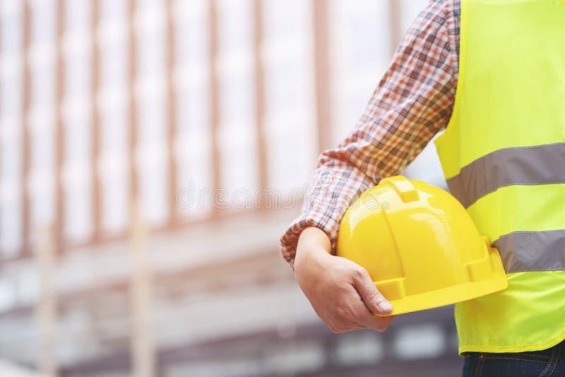 设计拿着卷轴式记录纸的男性建筑工人接近的在最前面的看法  免版税库存照片