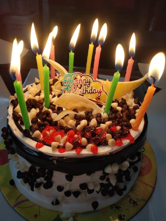 设计精美的生日蛋糕上放着点亮蜡烛,看上去很美。设计精美的生日蛋糕,上面插着点亮蜡烛,看ä 免版税库存图片