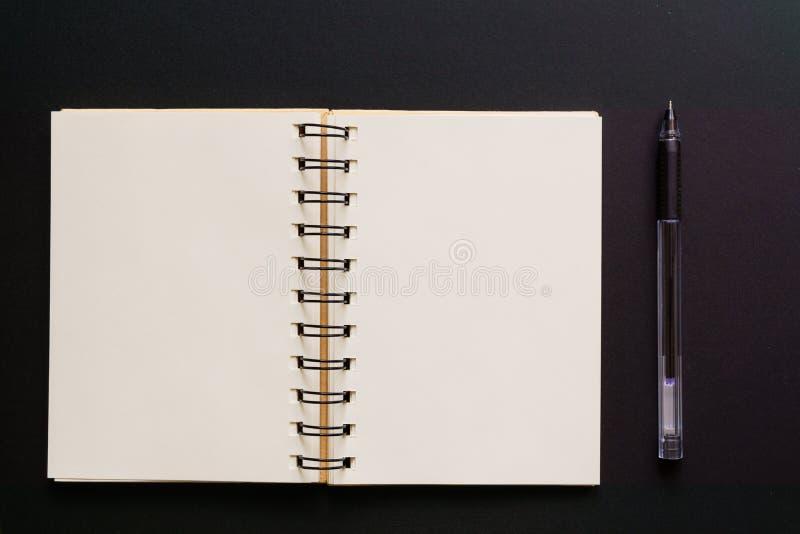 设计观念-空的卡拉服特笔记本和圆珠笔顶视图在黑背景的 ?? 免版税库存图片