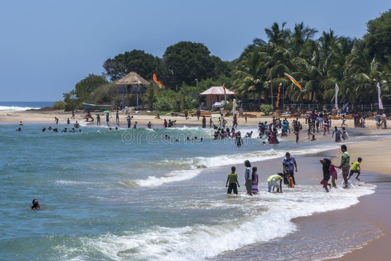 访客向阿鲁加姆湾在斯里兰卡享受游泳在海 库存照片