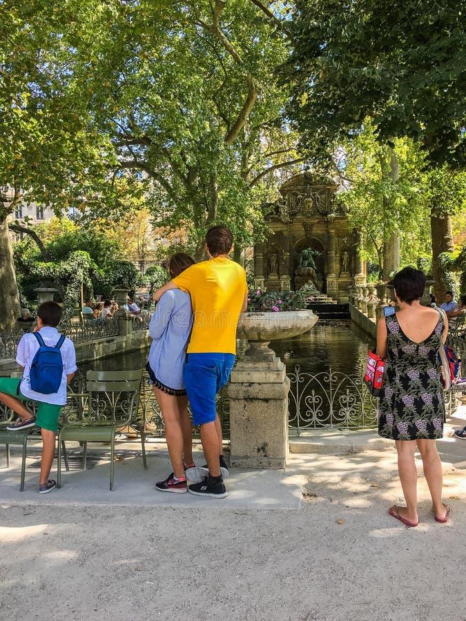 访客在卢森堡庭院里享用Medici喷泉在一个晴天 免版税库存图片