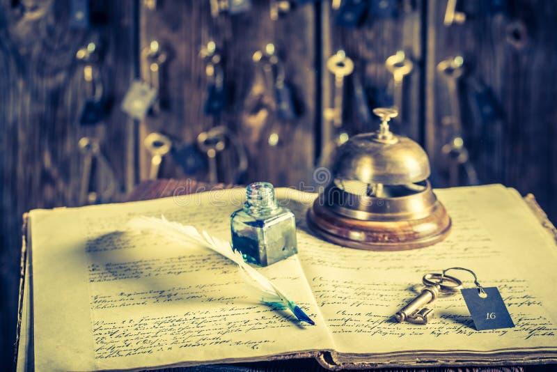 访客留名簿和钥匙房间的葡萄酒服务台的在旅馆里 库存图片