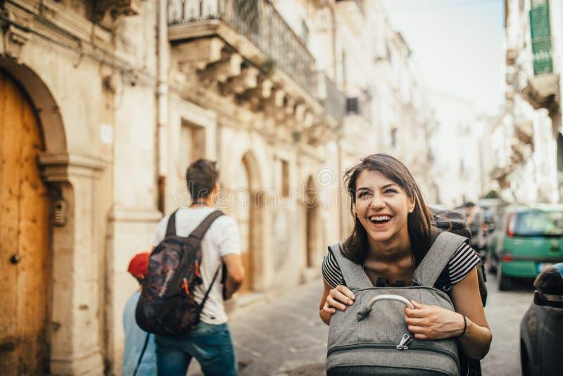 访问意大利的女性旅游背包徒步旅行者 妇女在西勒鸠斯,西西里岛 西勒鸠斯,Ortigia海岛老镇访客 目的地玻璃扩大化的映射旅行 免版税图库摄影