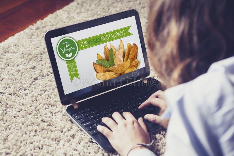 访问素食主义者餐馆网站的妇女在家说谎 库存图片